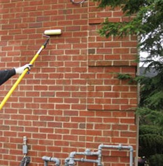 Technician applying Waterproof Sealing to Brick.  This seals the bricks to prevent cracking.